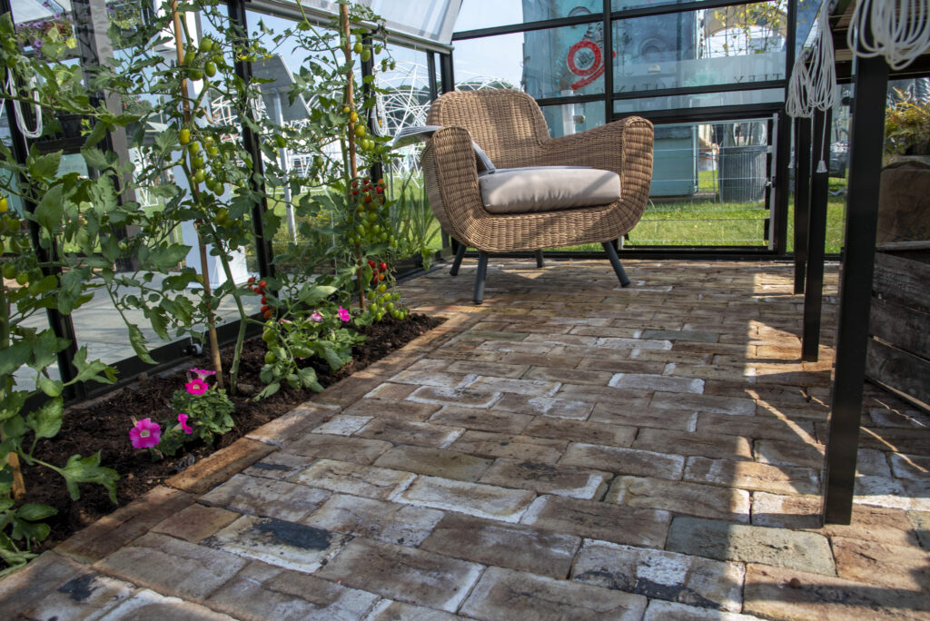 London Mixture Clay Pavers are paired with tomato plant in the flower beds and a wicker chair to create a traditional feel.