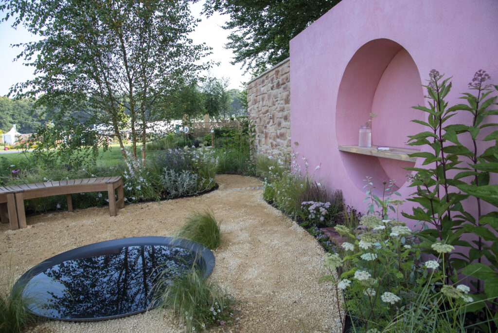 The Dreamscape Garden has a pink feature wall, circular water feature and curved benches. Our Seville Clay Pavers sit at the base of the wall to add the finishing touches.