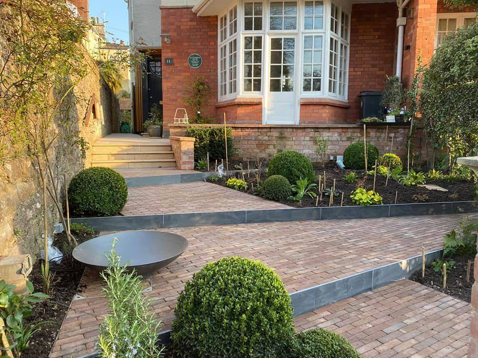 Bexhill Clay Pavers create unique. large steps with surrounding flower beds and natural stone edging.