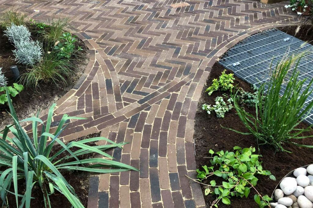 Rotterdam clay pavers are laid in curved patterns around flower beds to create pathways leading through the garden.