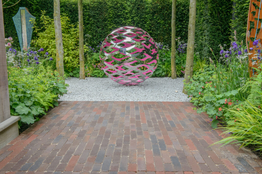 Clay pavers sat in front of a circular metal sculpture. Hedges sit behind the sculpture and vibrant planting surrounds the paving.