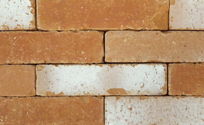 A close-up of Marigold Antique clay pavers from Chelmer Valley, in tones of tan, faded tan, with white