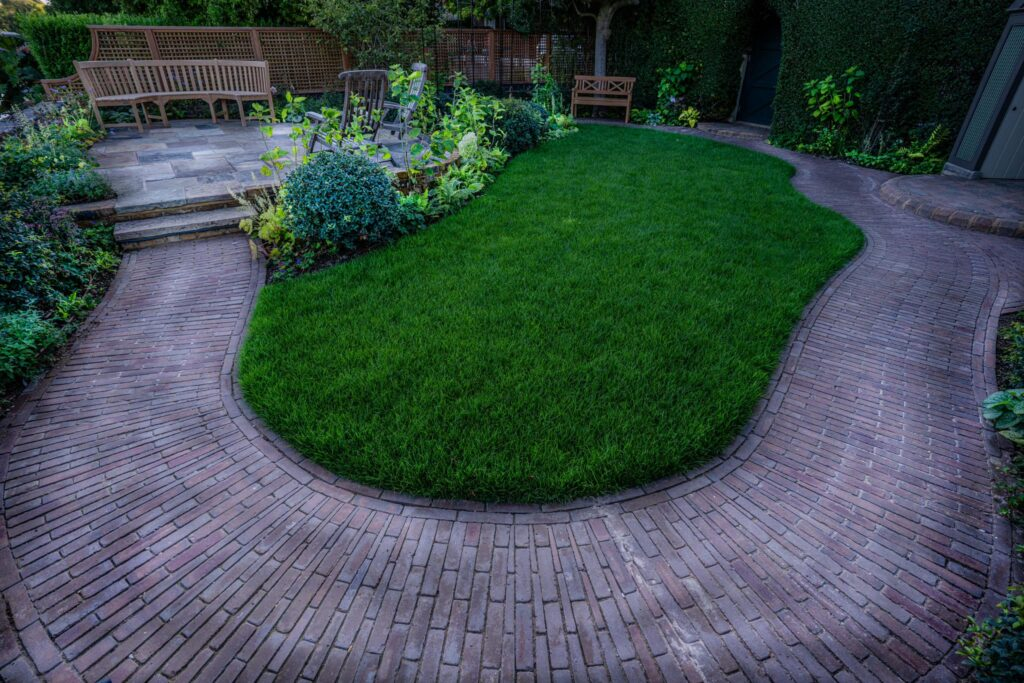 Our Abbey Dark Multi clay pavers form a circular path that lead to a small seating area and surrounds a grassed area.