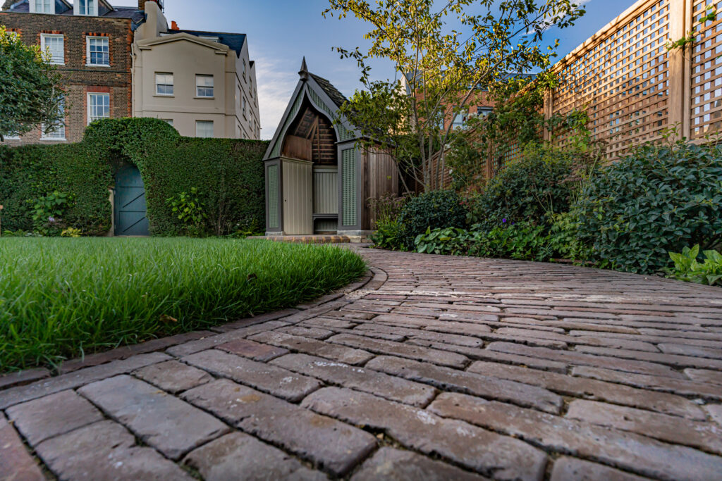 Our Abbey Dark Multi Clay Pavers are used to create a curved pathway. Hedges can be seen in the back ground, as well as fencing and planting.